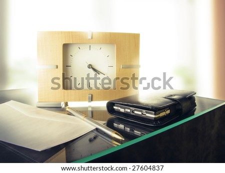 The morning of a businessman with modern alarm clock, a luxury pen and a portable device - stock photo