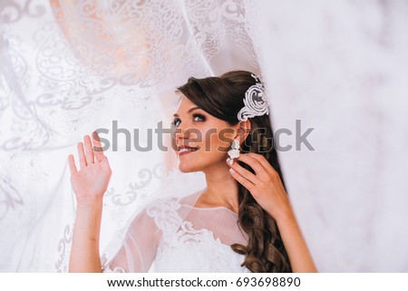 The morning of a happy bride near the window. Portrait of beautiful brunette bride in luxury white wedding dress posing, morning wedding preparation