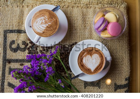the morning of the day in a cafe, two cups of cappuccino in white and purple flowers/ Two cups of cappuccino in white - stock photo