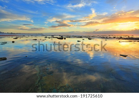 The morning sky is reflected in the ocean at Bateau Bay NSW Australia.  Heaven and earth in balance. - stock photo