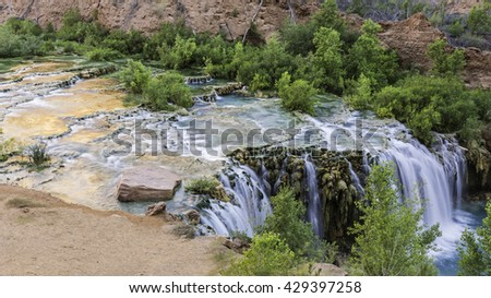 The morning sun bounces of the red cliffs and reflects off the travertine pools of Little Navajo Falls in Havasu Canyon in the Havasupai Indian Reservation. - stock photo