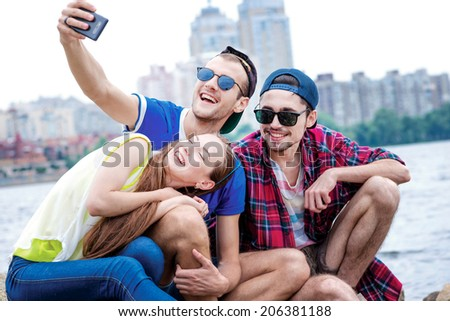 The most beautiful day with friends. Three friends sitting and laughing at the river and pictures of each other on a cell phone - stock photo