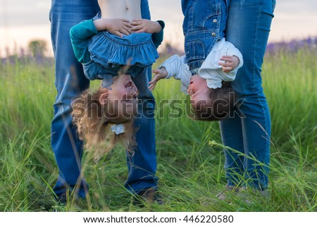 The mother and father hold their daughters upside down - stock photo