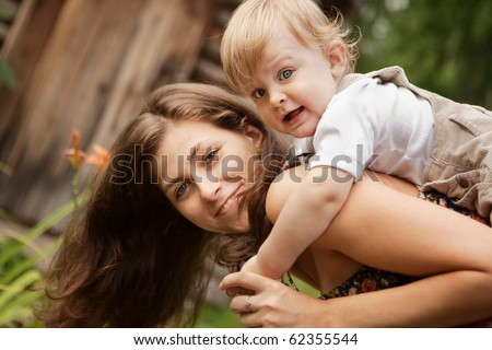 The mother carries a small son on her back - stock photo