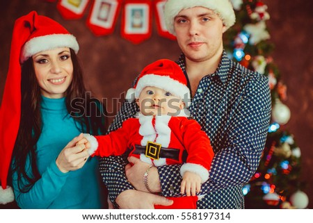 The mother,father and small son stand near Christmas tree
