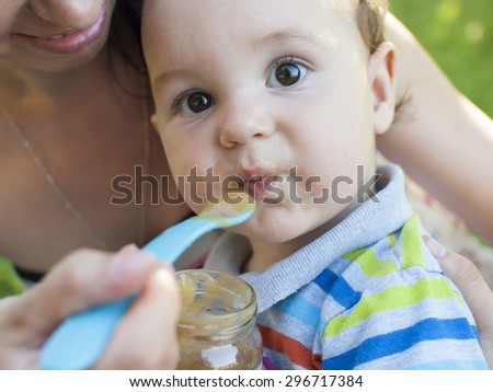 The mother feeds her young child from a spoon on the street. - stock photo