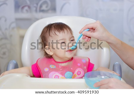 the mother feeds her young child with a spoon delicious lunch of fruit puree - stock photo