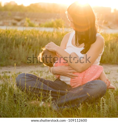 The mother feeds the young baby in the countryside in the sunlight at sunset. Breast feeding. Summer holiday.