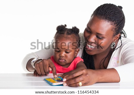The mother is teaching her daughter some alphabet letters.