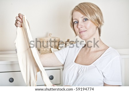 The mother prepares the baby-linen for the child - stock photo