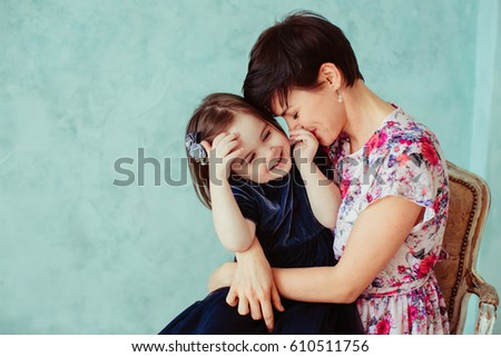The mother with daughter embracing and sitting on the chair