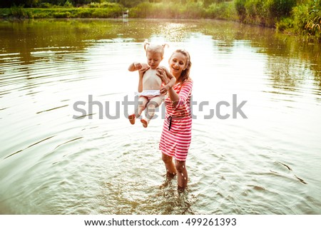 The mother with  daughter stand in  the lake