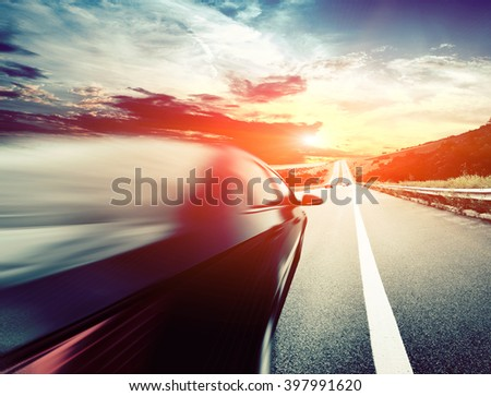 The motion blurred car on asphalt road - stock photo