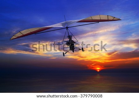 The motorized hang glider in the sunset above sea - stock photo