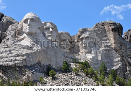 The Mount Rushmore National Monument in the Black Hills of South Dakota. Blue sky with the afternoon sun casting shadows across the famous faces of Lincoln, Roosevelt, Jefferson, and Washington. - stock photo