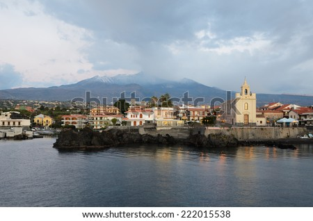 The mountain Etna is smoking above the Italian coastal town Acireale at sunrise.