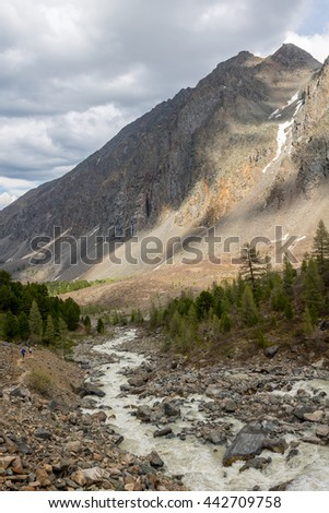 The mountain river, against the woody mountains, originating from a thawing glacier. Western Siberia, Altai - stock photo