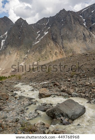The mountain river, against the woody mountains, originating from a thawing glacier. Western Siberia, Altai mountains. - stock photo