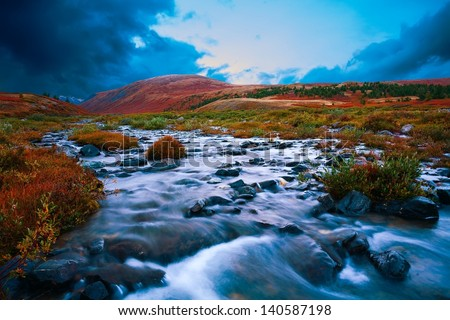 The mountain river in a taiga on sunset - stock photo