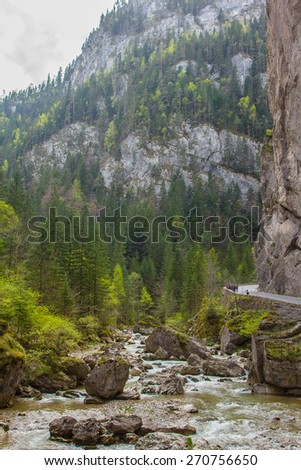 The mountain river with boulders at the foot of the cliff to the road. It is in the Carpathian Mountains, Romania, Transylvania. - stock photo