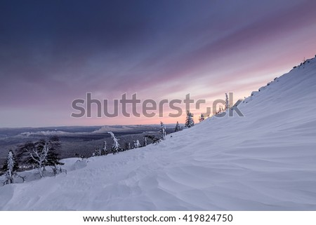 The mountain slope with stones are covered by snow in the winter evening light on the backdrop of the hazy distance, Kumardak range, South Urals, Russia. - stock photo