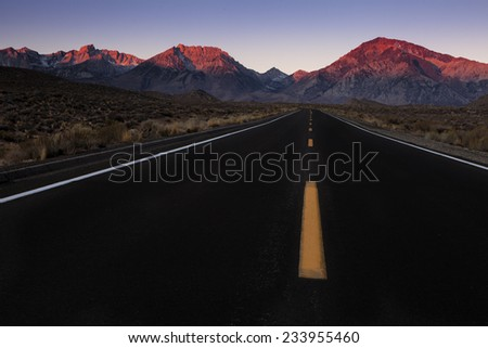 The Mountains are calling.  A highway leading to the mountains at dawn.  The morning light casts alpenglow on the peaks. - stock photo