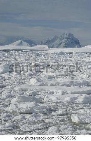 The mountains of the Antarctic winter in the background covered with ice of the strait. - stock photo