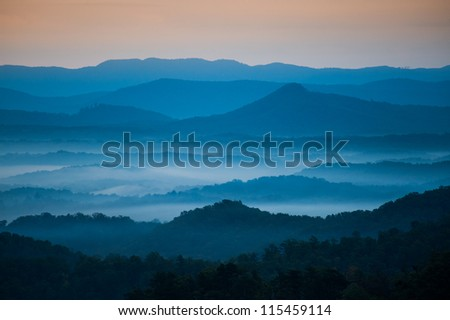 The mountains on the Blue Ridge Parkway welcome the morning with light and mist. Fog is forming in the valley as the sun comes up lighting up the day. - stock photo