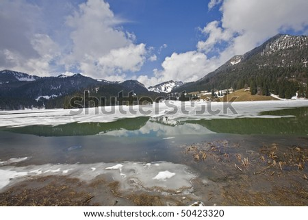 the mountains reflect in the iced water of the lake in spitzingsee germany