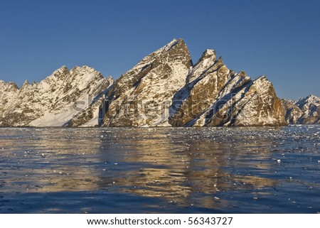 the mountains row high from the sea in the coasts of greenland - stock photo