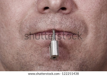 The mouth is closed with a padlock. The symbol of silence and censorship. - stock photo