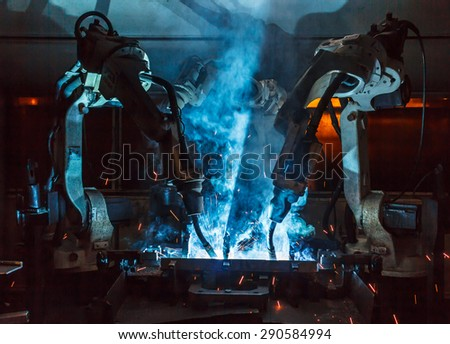 The movement of the robot welding in an auto parts factory. - stock photo