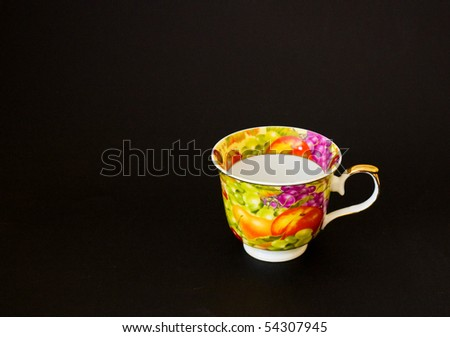 The multi-coloured ornamented tea cup on a black background (Russian style) - stock photo