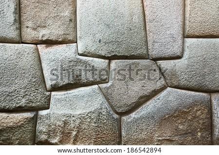 The multi-sided granite stones in ancient Inca wall street Hatunrumiyoc - Cusco, Peru - stock photo