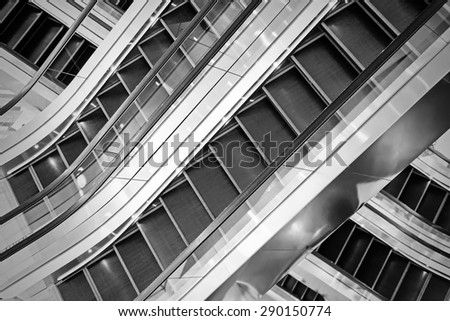 The multiple steps and directions of an escalator in the modern shopping mall , black and white background - stock photo
