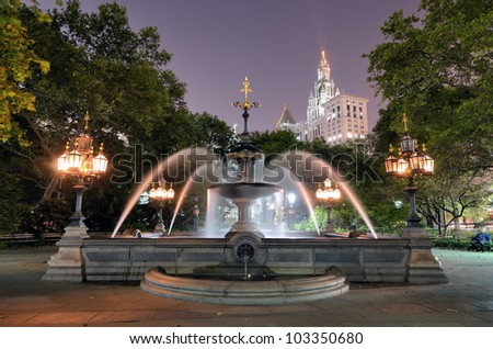 The Municipal Building towers over the fountain in City Hall Park in Lower Manhattan New York CIty. - stock photo