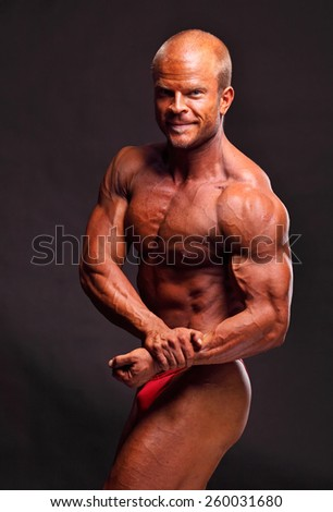 The muscular male bodybuilder flexing biceps on black background - stock photo
