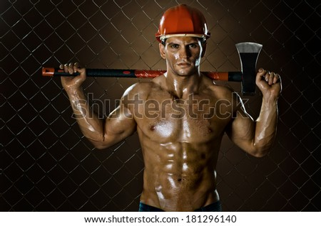 the muscular  tired worker chopper man, in  safety helmet  with big heavy ax in hands, on netting fence background - stock photo