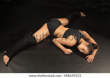 The  muscular young woman athlete  sitting on the split on black background.