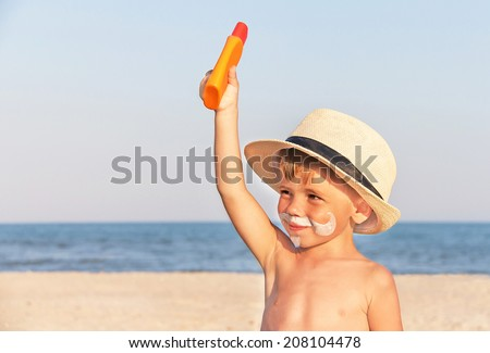 The mustache drawing sunscreen (suntan lotion) on hipster baby (boy) face. Caucasian smiling child (kid) is holding container of sunscreen on beach. Trendy fashion concept. Copy space, close up.  - stock photo