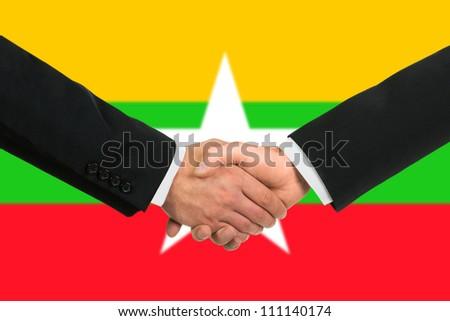 The Myanmar flag and business handshake - stock photo