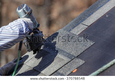 The nail gun is used to attach shingles to the roof. - stock photo
