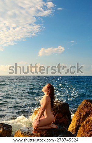 The naked girl near the storming sea - stock photo