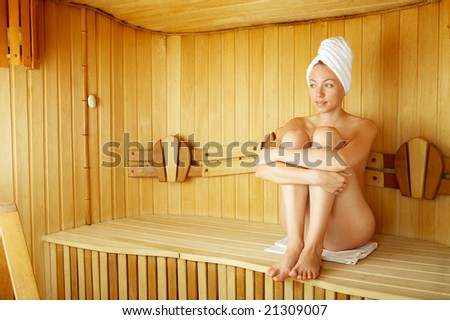 The naked girl sits on a bench in a sauna - stock photo