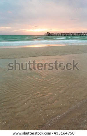 The Naples Pier sunset in the Gulf of Mexico, Southwest Florida, USA. Amazing spot of the sun coming down at blue hour in this idyllic place for family vacation and relax.Twilight, Florida, USA - stock photo
