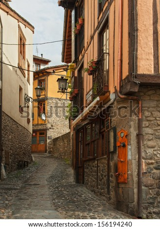 The narrow street with old houses in Potes, Cantabria, Spain. - stock photo