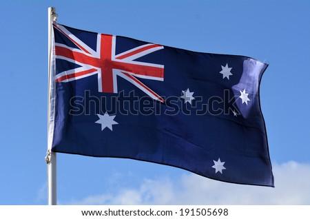 The National flag of Australia against blue sky. - stock photo