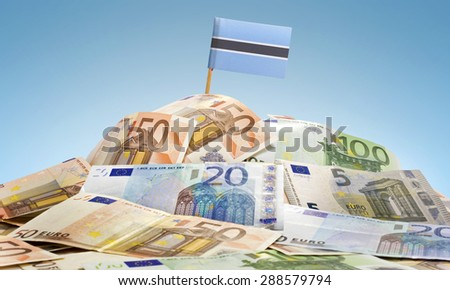 The national flag of Botswana sticking in a pile of mixed european banknotes.(series) - stock photo