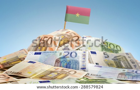 The national flag of Burkina Faso sticking in a pile of mixed european banknotes.(series) - stock photo