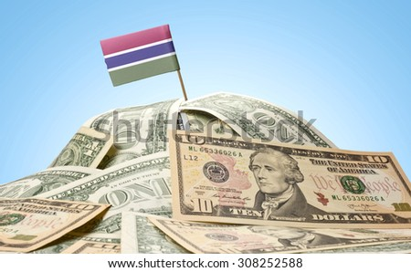 The national flag of Gambia sticking in a pile of american dollars.(series) - stock photo